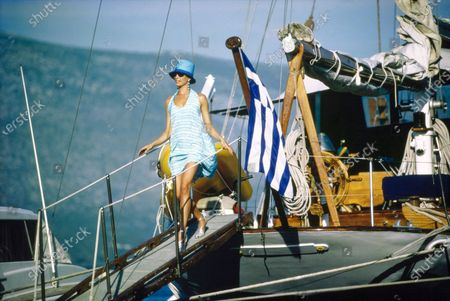 Model Dana Patrick, getting off boat flying the Greek flag on the Greek Isles. She is wearing a white and turquoise rayon print trapeze dress by Patricia Clyne, sunglasses from Optic Studio, long earrings from Isaac Manevitz for Ben-Amun, silver sandals from Manolo Blahnik, and a blue hat by Eric Javits. Hair and makeup by Giorgio for Suga Salon, NYC. Dana Patrick