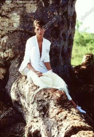 Model Christy Turlington, sitting on the roots of a tree on Funzi Island, Kenya, wearing a white viscose single-breasted pantsuit by Helmut Lang. Hat (on root) by Hat Attack. Hair by Didier Malige for Jean Louis David. Makeup by Marie-Josee Lafontaine. Christy Turlington