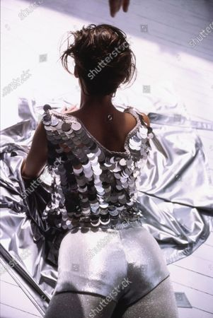 Model Carrie Coffey laying on her stomach, seen from behind. She is wearing medieval-inspired metal top (cotton and plastic) by Joan Vass, silver lamé shorts (rayon, polyester, and metal) by Betsey Johnson, and silver tights. She is laying on a silver raincoat by Drizzle. Hair by Mark Garrison for Jean Louis David. Makeup by Marie-Josée Lafontaine. Carrie Coffey