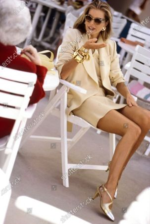 Model Vera Cox, seated on a folding chair in an outside plaza, wearing a white wool and angora polo sweater as a blouse, under a white wool jacket and skirt, by Sonia Rykiel. Sunglasses by Christian Lacroix. Earrings by Gerard Yosca. Shoes by Chanel. Wrist jewelry: Segmented gold cuff by Frances Patiky Stein, mosaic bracelets by Roxanne Assoulin, chain with discs by DKNY, watch by Chopard. Hair by Donald Mikula for Pipino-Buccheri. Makeup by Sonia Kashuk. Vera Cox
