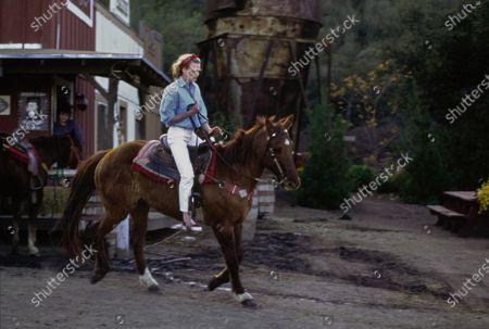 Actress Robin Wright on a brown horse with a white star marking on the forehead, riding away from an outpost building; a rusty water tower stands in the background. Wright is wearing a light blue denim chambray shirt by Banana Republic and white Calvin Klein jeans. Accessories: bandanna by Randi Zinz and Marcia Lyons for Two City Girls; diamond stud earrings by Harry Winston; red sneakers by Vans. Hair by Christiaan. Makeup by Sonia Kashuk for Aveda. Robin Wright