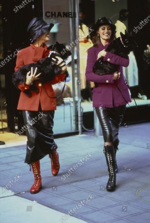 Two models, Nadège du Bospertus, left, and Susan Holmes, right, carrying two black Scottie dogs in their arms while walking down street wearing brightly colored wool jackets and black leather skirts, all by Karl Lagerfeld for Chanel. Bospertus is in a red jacket and red boots. Holmes is in a red-violet jacket and black boots. On both models: black leather bucket hats, earrings, and calf high lace up leather boots by Chanel. Hair by Troy Alterman for Oribe at Elizabeth Arden. Makeup by Moyra Mulholland. Susan Holmes, Nadege du Bospertus