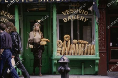 Model Claudia Schiffer walking out of Vesuvio Bakery, New York, New York, holding several loaves of bread under her left arm and a small parcel in her right hand. She is  wearing a tan ribbed wool sweater set and black leather skirt, all by Isaac Mizrahi. Accessories: tan beret by Kangol; earrings, belt, and gloves by Isaac Mizrahi; shoes by Manolo Blahnik. Hair by Troy Alterman for Oribe at Elizabeth Arden. Makeup by Moyra Mulholland. Claudia Schiffer