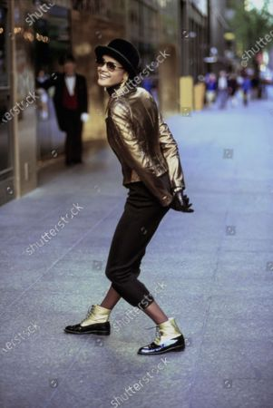 Model Nadège du Bospertus posing on the city street in New York, New York, her hands clasped behind her back and knees bent. She is wearing a bronze leather jacket with quilted sleeves and mock-turtleneck black viscose dress, both by Christian Lacroix. Accessories: black bowler hat by Makins Hats; gold earrings, sunglasses, black gloves, and black and gold ankle boots by Christian Lacroix. Hair by Troy Alterman for Oribe at Elizabeth Arden. Makeup by Moyra Mulholland. Nadege du Bospertus