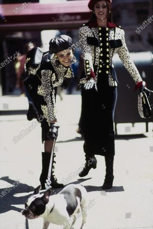 Two models, Nadège du Bospertus, left, and Susan Holmes, right, walking a French bulldog while walking down the street. They are both wearing Dalmatian spotted suits by Gemma Kahng, cotton and viscose jackets with gold button embellishments over wool and Lycra black midi length skirts. On both models: matching hats, bags, gloves, and high heeled boots by Gemma Kahng. Hair by Troy Alterman for Oribe at Elizabeth Arden. Makeup by Moyra Mulholland. Susan Holmes, Nadege du Bospertus