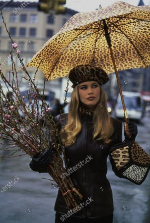 Model, Claudia Schiffer, standing beneath a leopard umbrella in Union Square Park in New York, New York, holding budding branches in her left arm. She is wearing a tailored black leather jacket by Louis Dell'Olio for Anne Klein Collection. Accessories: umbrella by Mespo Umbrellas Ltd.; beret by Eric Javits; scarf and gloves by Adrienne Landau; bag by Renaud Pellegrino. Hair by Troy Alterman for Oribe at Elizabeth Arden. Makeup by Moyra Mulholland. Claudia Schiffer