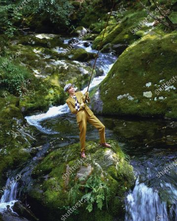 Model Christy Turlington stands on a large mossy rock in the middle of a stream, fishing, in Wales, United Kingdom. She is wearing an orange and green checked suit and large navy and white check silk tie with a white and navy dotted acetate and silk shirt by Emporio Armani. Accessories: navy and white check flat cap by Emporio Armani; leather brogue shoes by Ralph Lauren Footwear. Hair by Didier Malige for Frederic Fekkai at Bergdorf Goodman. Makeup by Sonia Kashuk for Aveda. Christy Turlington