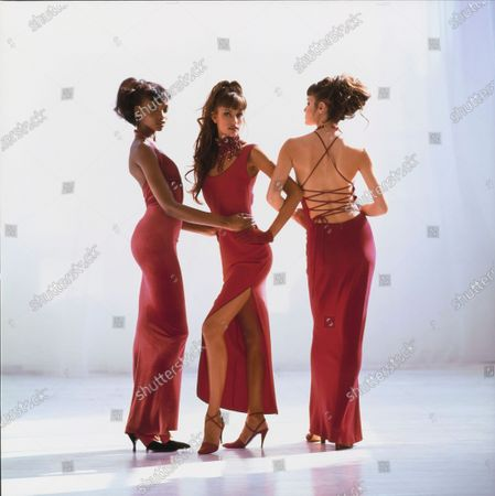 A trio of models posed in front of a white studio backdrop. Beverly Peele, left, puts her hands on the waist of Susan Holmes, middle, who hooks elbows with Claudia Mason, right, with all three women in long red dresses. Peele is wearing a red ankle length velvet and silk gauze halter dress by Martin Price & Juan Pisonero for Giorgio di Sant'Angelo and shoes by Sidonie Larizzi. Holmes is wearing a red acetate and viscose tank dress with side slit by Sylvia Heisel with a collar by Jordan Doner, bib necklace by Maria Ferra, and shoes by Anne Klein Footwear. Mason is wearing a red back-laced cashmere and wool jersey dress by Louis Dell'Olio for Anne Klein Collection and unidentified shoes. Hair by Oribe at Elizabeth Arden. Makeup by Marie-Josee Lafontaine. Beverly Peele, Susan Holmes, Claudia Mason