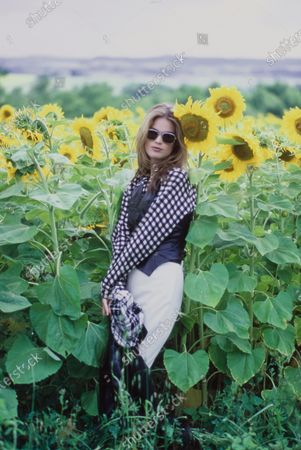 Stock Image of Model Meghan Douglas standing among a field of sunflowers. She is wearing a gingham check black and white cotton shirt by Georges Marciano with a black leather vest and white wool and Lycra jodhpurs, both by Ralph Lauren Collection. Accessories: black and white plaid scarf; sunglasses by Jean Paul Gaultier for Optical Affairs. Hair by Satoru Nagata for Oribe at Elizabeth Arden. Makeup by Sonia Kashuk for Aveda. Likely photographed at the Chateau de Beaulieu near Perigueux, Dordogne, France, the home of furniture designer and craftsman Andre Dubreuil, as part of a photoshoot from the October 01, 1992 issue, page 308. Meghan Douglas