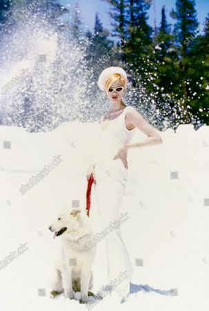 Model Kristen McMenamy, with a dog on a snow-covered hill, wearing a white stretch cotton and viscose velvet tank dress from Istante by Gianni Versace, and white sunglasses by Arnet.Hair by Didier Malige for Frederic Fekkai Beaute. Makeup by Mary Greenwell. Kristen McMenamy