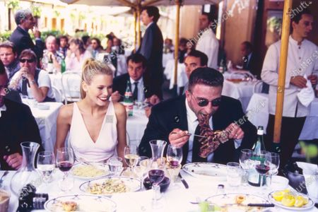 Model Claudia Schiffer dines on pasta alfresco in Rome, Italy, with an unidentified male model as her 'bodyguard' next to her, eating a large steak. She is wearing a bare, blush-pink v-neck sheath dress of silk and spandex by Donna Karan New York. The 'bodyguard' model sitting next to her wears a black Valentino suit. Hair by Didier Malige for Frederic Fekkai at Bergdorf Goodman. Makeup by Dick Page, including Revlon's Super Lustrous Lipstick in Certainly Red. Claudia Schiffer