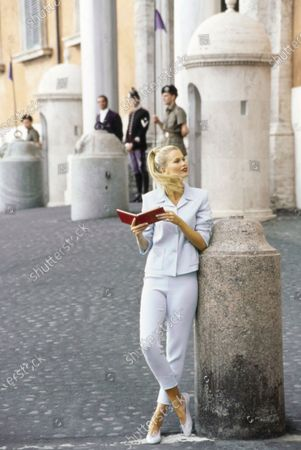 Model Claudia Schiffer leans against an upright marble barrier with red guide book in front of a building with a guarded entrance in Rome, Italy. She is wearing capri pants and jacket with patch pockets in aqua blue acetate and viscose by Mark Eisen with pale ballet flats by Just Libby. Hair by Didier Malige for Frederic Fekkai at Bergdorf Goodman. Makeup by Dick Page. Claudia Schiffer