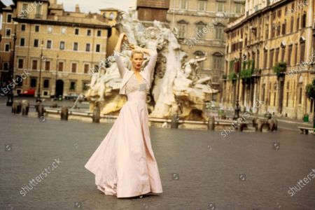 Stock Image of Model Claudia Schiffer tugs on her hair as she walks in front of the Fontana dei Quattro Fiumi in Piazza Navona in Rome, Italy. She is wearing a full-skirted pink cotton and silk taffeta evening dress with a beaded bodice by Jacques Fath with a pink cashmere cardigan by TSE Cashmere. Hair by Didier Malige for Frederic Fekkai at Bergdorf Goodman. Makeup by Dick Page. Claudia Schiffer