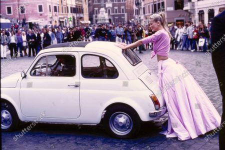 Stock Picture of Model Claudia Schiffer leans against a 1967 white Fiat 500 on the street in Rome, Italy. She is wearing a waist-tied pink wool cardigan by Genny over a long, full pink Taroni silk taffeta skirt by Atelier Versace. Hair by Didier Malige for Frederic Fekkai at Bergdorf Goodman. Makeup by Dick Page. Claudia Schiffer