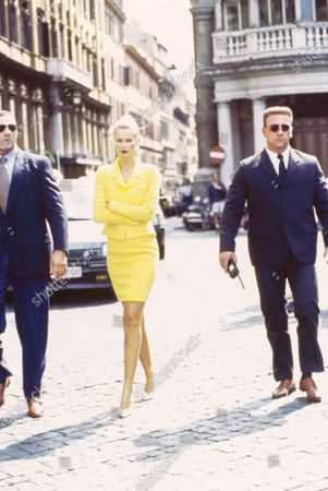 Stock Photo of Model Claudia Schiffer walks with her arms crossed between two suited 'bodyguard' models on the street in Rome, Italy. She is wearing a bright yellow wool skirt suit by Karl Lagerfeld for Chanel with white heels by Manolo Blahnik. The 'bodyguard' models standing on either side of her wear Valentino suits. Hair by Didier Malige for Frederic Fekkai at Bergdorf Goodman. Makeup by Dick Page. Claudia Schiffer