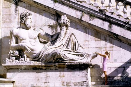 Model Claudia Schiffer stands at the foot of a large reclining Roman statue, her hands up on the marble toes. She is wearing light pink sleeveless wool crepe shift dress by Genny and pink patent leather high heels by Manolo Blahnik. Hair by Didier Malige for Frederic Fekkai at Bergdorf Goodman. Makeup by Dick Page. Claudia Schiffer