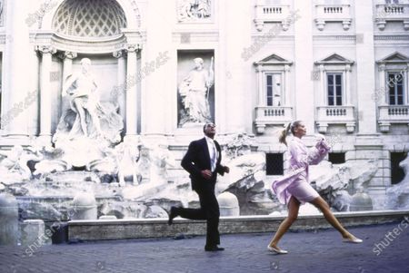 Model Claudia Schiffer trots in front of the Trevi Fountain, followed by her 'bodyguard' in Rome, Italy. She is wearing a pink silk raincoat covered in white polka dots by Bill Blass with a light pink silk shantung skirt made with B&J fabrics from Vogue Pattern #9187. Accessories: pink Chanel purse; pale ballet flats by Just Libby. The 'bodyguard' model jogging behind her wears a black Valentino suit. Hair by Didier Malige for Frederic Fekkai at Bergdorf Goodman. Makeup by Dick Page. Claudia Schiffer