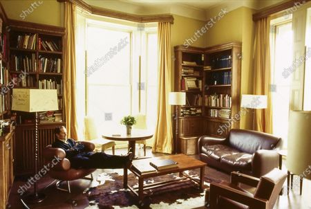 """Designer Nick Ashley, son of Laura Ashley, sitting in his London apartment. Carved wooden bookshelves (one of which is inscribed with the motto """"YOU ARE ON LOAN FOR NOUGHT IS OURS"""") hold Laura Ashley's design library. A cowhide rig sits at the center of the room, with a plain wooden coffeetable atop it. Nick Ashley is seated in Eileen Gray's 1925 """"Bibendum"""" chair, a stack of semicircular leather-upholstered cusions on a steel base; next to it is a tall lamp with a spiral-carved stand and notes scrawled on the square shade. On the other side of the room are Matthew Hilton's 1991 leather-covered """"Balzac"""" sofa and Thomas Rietveld's 1935 """"Utrecht"""" chair. Nick Ashley"""