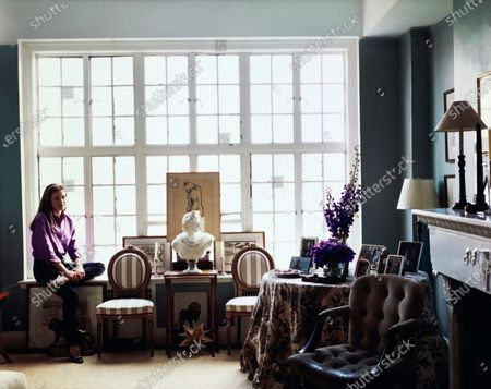 Interior decorator Alexa Hampton, daughter of decorator Mark Hampton, in her New York apartment. Immediately in front of the windows is a symmetrical arrangement of a pair of oval-backed wooden chairs with striped upholstery by a small table holding a neoclassical bust, and framed sketches on the window ledge. Next to a fireplace is a round table with a floral motif tablecloth, holding several framed pictures. Next to the table is a brown suede upholstered armchair. Alexa Hampton