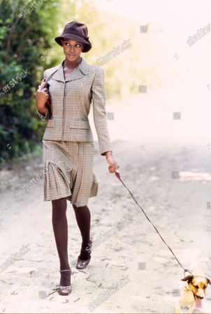 Model Naomi Campbell, walking a dog on a country road, wearing a plaid wool jacket and pleated skirt by Oscar de la Renta with a brown hat by Jacqueline Lamont and handbag and shoes by Prada.Hair by Christiaan and Ellin LaVar. Makeup by Fulvia Farolfi. Naomi