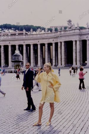 Model Claudia Schiffer poses with one hand on her hip and takes a picture with a black camera while standing in Piazza San Pietro at the Vatican. She is wearing a bright yellow and white striped mini sheath dress of polyamide, cotton, and lycra by Karl Lagerfeld and a yellow and white checked silk trench coat by Bill Blass with white flip flops that have yellow flowers on the vamp by Lilly Putlizer. The 'bodyguard' model standing behind her wears a black Valentino suit. Hair by Didier Malige for Frederic Fekkai at Bergdorf Goodman. Makeup by Dick Page. Claudia Schiffer