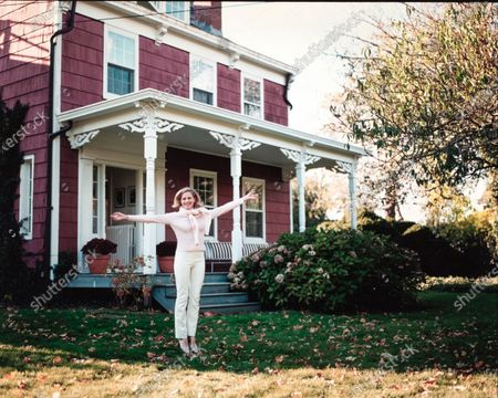 Architect Alison Spear standing in front of her Long Island farmhouse. The house is clad in red clapboard with white trim around the windows and cornices. A sheltered porch, its canopy supported by thin carved wood columns, runs the length of the front of the house. Alison Spear