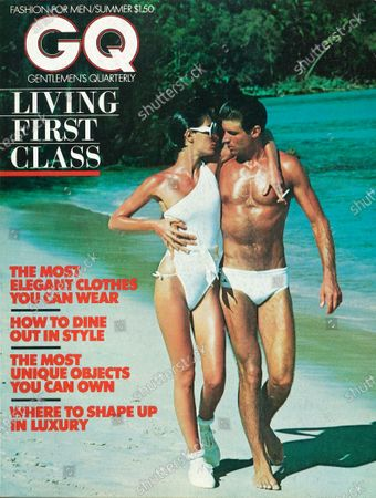 Stock Picture of GQ June 01, 1976 Magazine Cover featuring: White with red logo over photo of two models walking on the beach, he wears a polyester swimsuit by Catalina and a sterling silver chain and pendant by Brusca-Dante, she wears a suit by Giorgio Sant' Angelo and sunglasses by A.R. Trapp. Summer Issue.