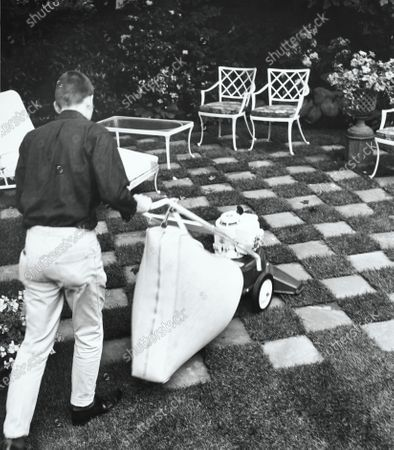 Man using gas-powered lawn vacuum.
