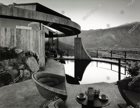 House Spectacular: a pool partly sheltered by the dome, and a terrace off the living room, with view of landscape, at a house built in Palm Springs, California by John Lautner for Arthur Elrod.