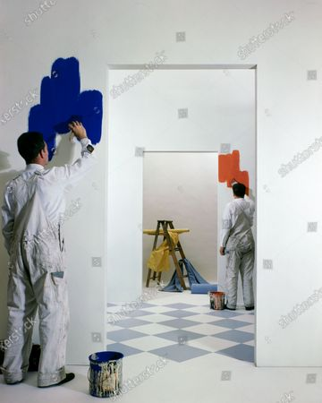 Seen through a series of doorways, alternating sides of the doorways, in each of the four rooms is a house-painter beginning to paint each white room in a very bright blue, red, yellow and green respectively.