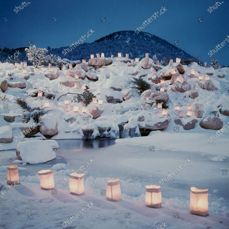 Garden at St. John's College at Sante Fe, farolitos - candles are cupped in sand in paper bags - weave a Christams garland for the frozen pool and snow-capped rockery.