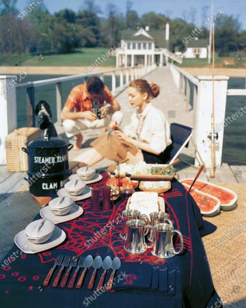 A dock picnic clambake with Mexican tablecloth in blue and red, pewter tankards, white flatware, and watermelon for desert. A Man squats in background taking a picture of woman in chair.