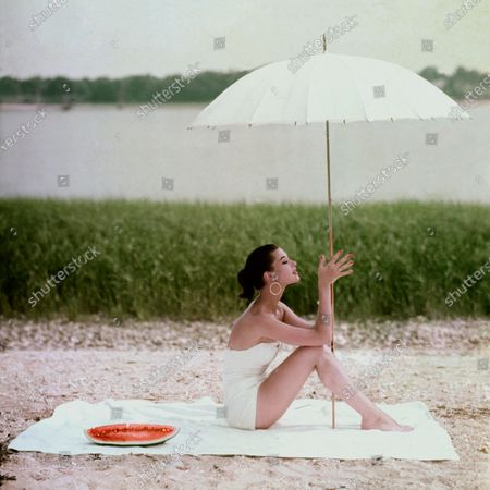 Model Barbara Mullen in white suit sunbathing on white towel under white umbrella with green of grasses beyond and the blue water in the background. Barbara Mullen