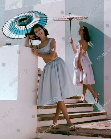Two models standing beneath colorful parasols: (left) one wearing seersucker dress by Sportwhirl; the other wearing gingham separates by Junior Sophisticates, flower push-up bracelets by Sandor Goldberger, and sandals by Bernardo.