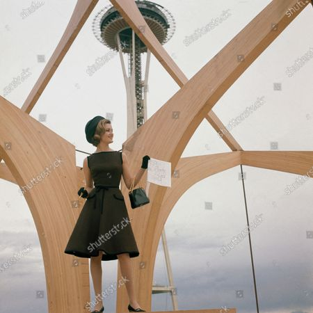 Sue Richard, fashion expert, at the World's Fair Space needle, wearing a chocolate brown dress of Ekna rayon in Folkner linen weave by Junior Accent and shiny black accessories.