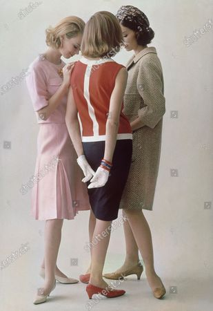 Three models in a huddle: (l to r) model in pale pink linen dress by Sportswhirl, with greige calf shoes, model in sleevless red knit overblouse and navy skirt by Goldworm, with red shoes by Millerkins, and model in camel wool tweed coat by Dani Junior, with shoes by Millerkins.