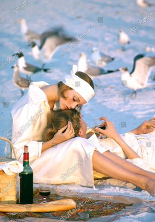 Man and woman dressed in white, and lounging on beach with wine in spread for Midsummer's Eve Party for Lover's.