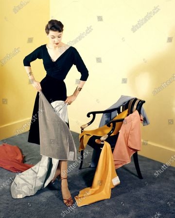A woman wearing a black dress is holding two pieces of gray fabric while a variety of orange, pink and blue swatches are strewn on a chair and a red piece is on the gunmetal gray carpet; the walls are yellow.