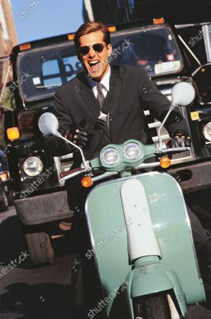 Stock Photo of Male model, wearing a suit, riding a turquoise Vespa scooter.