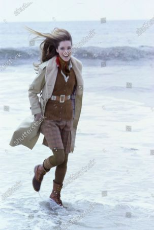 Model walking on beach, wearing belted, camel, cotton coat with acrylic pile lining, by Daniel Hechter for Fox Run, camel check, wool walking skirt by Gordon of Philadelphia, pigskin belt by Elegant, Grandoe wool gloves, Glentex paisley scarf, and Bass boots.