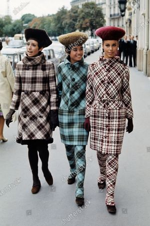 Three models walking down street wearing argyle and plaid coats. suits and matching stockings, by Cardin, with fuzzy high rounded helmets.