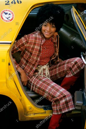 Gwen Jenkins, fashion assistant, smiling at camera and getting out of taxi cab, wearing red plaid gaucho suit by Cacharel, T-shirt by Ronald Kolodzie, and Tres Toros belt. Gwen Jenkins