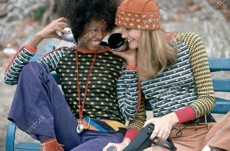 Two models sitting on a park bench, sharing headphones: Left, in a shirt with mis-matched body and sleeves, by Ingeborg Hecht & Kai Lofton, with purple jeans by Levi's for Gals, watch by Randolph Graff and belt by Vacher; Right, in shirt with zig-zag sleeves by Ingeborg Hect & Kai Lofton, orange jeans by Plushbottoms, belt by Buxton and orange star-studded hat by Ronald Kolodzie.