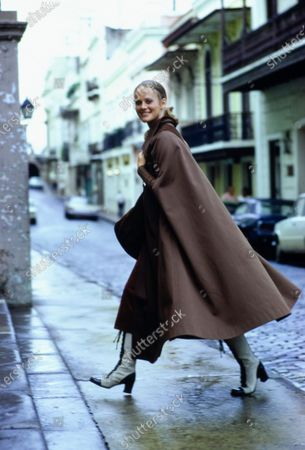 Stock Image of Model crossing city street wearing a wide brown cape laced up the front with leather thong by Calvin Klein. Bag by Lederer, boots by Vendome for Jack Hinton International. Margareta Arvidsson