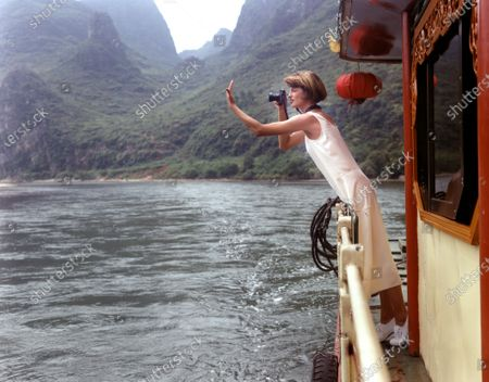 Model, Linda Evangelista, wearing a cream color silk tank dress with horizontal seams, by Calvin Klein, leaning over the rail of a boat, taking a picture, on the Li River, in Guangxi, China. Linda Evangelista