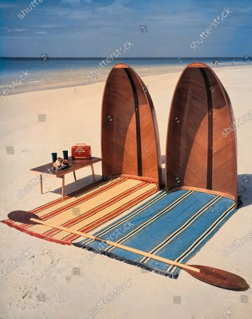 A Pixie collapsible boat, divided in two and upended in sand. At the helm, two beach towels with East Indian stripes, create sun shields; Folding beach table to the side, oar laid across towels.