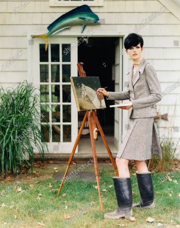Model, Stella Tennant, wearing a black, white, and pastel tweed suit, by Marc Jacobs, with tall black rubber boots, standing outside of a house, painting the picture of a horse. Stella Tennant