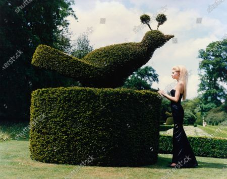 Model Kirsty Hume, wearing a long strapless black silk dress by Oscar de la Renta, standing on the grounds of Cliveden House, in England, beside a large topiary bird. Kirsty Hume