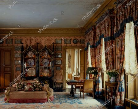 Drawing room in the Paris apartment of Princess Firyal of Jordan designed by Geoffrey Bennison, featuring an eighteenth century Gothic-style black lacquer cupboard with its original floral chintz lining, a Ziegler Persian carpet, a Victorian confidente with deep pink tassel trim and needlepoint cushions, and hand painted window shades.