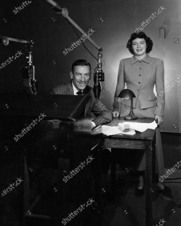 Composer Hoagy Carmichael seated with his secretary on his weekly radio show, Shirlee Turner, standing, wearing a worsted crepe suit with a full gored skirt by Roth LeCover. Hoagy Carmichael
